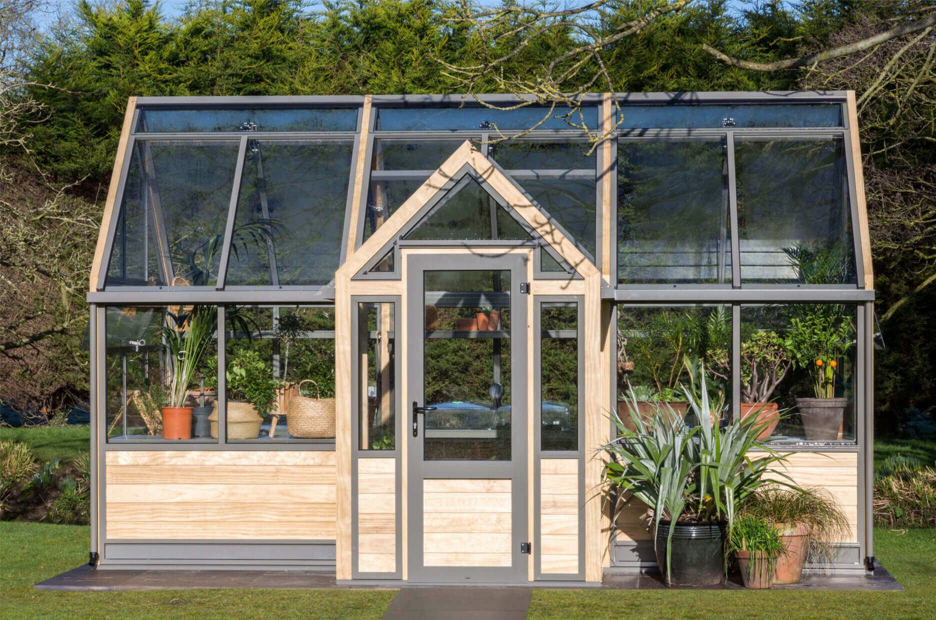 Attractive wooden greenhouse with central porch