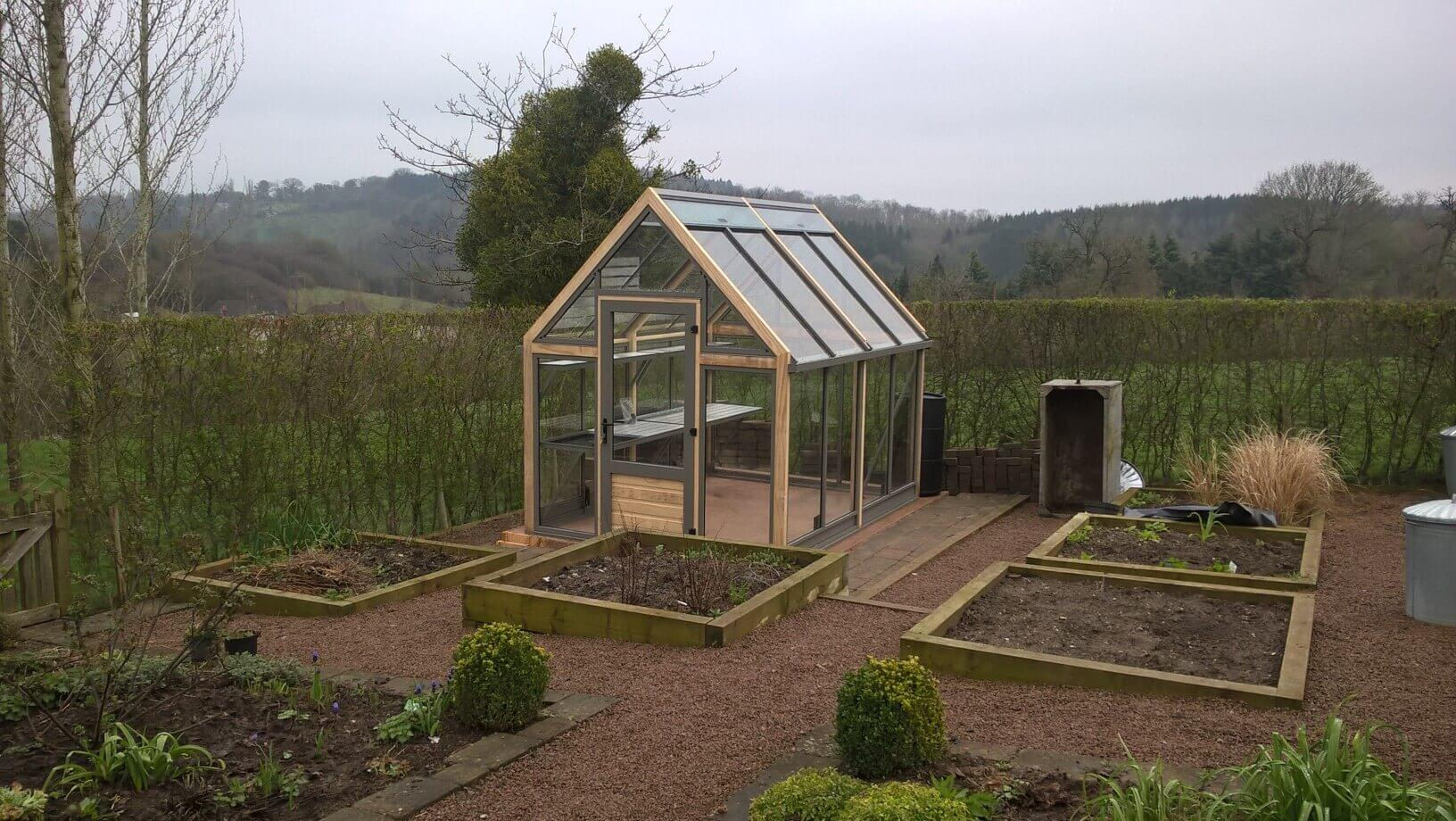 Recently landscaped kitchen garden with greenhouse