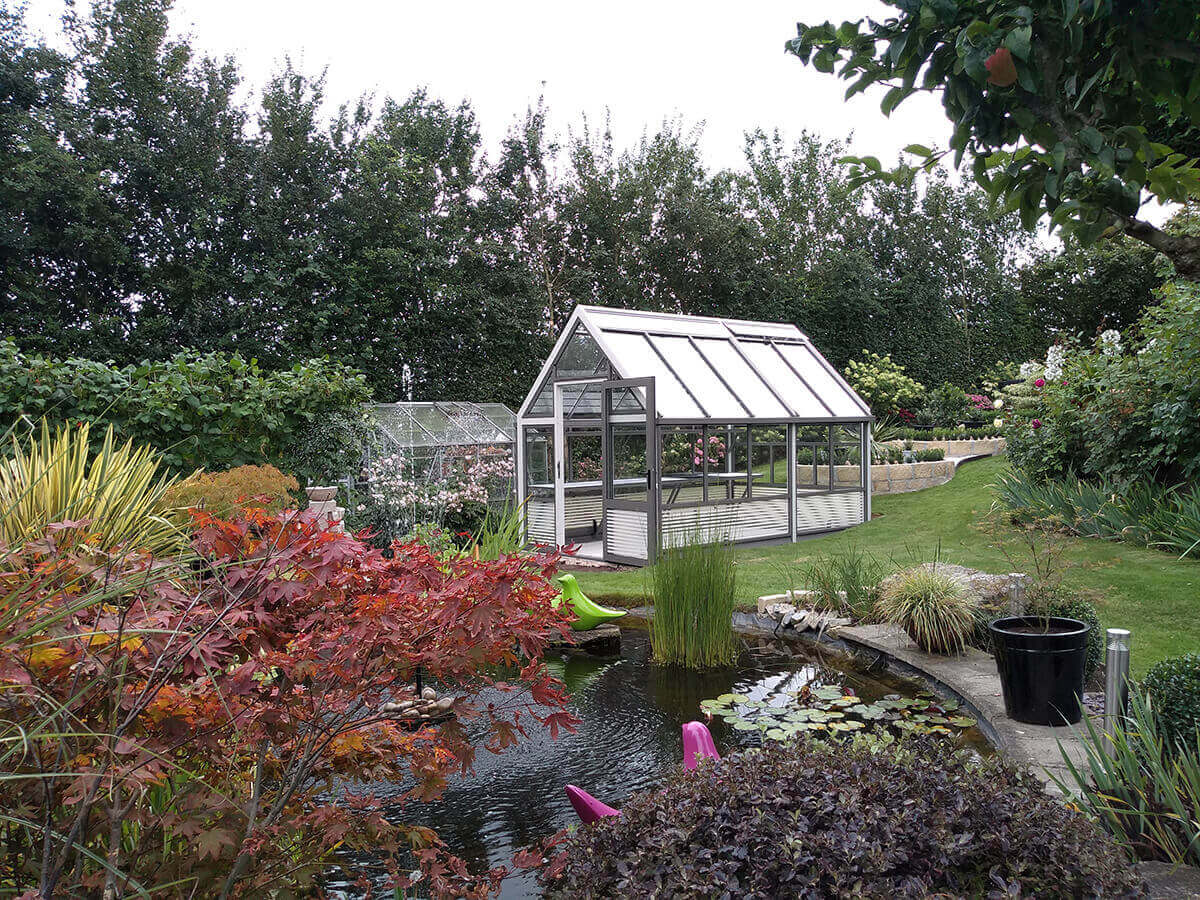 Modern aluminium greenhouse beyond pond