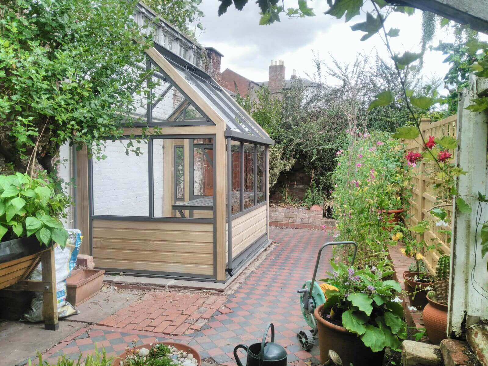 narrow wooden lean-to greenhouse