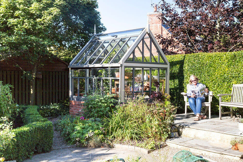 Small victorian greenhouse on a dwarf wall
